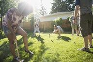 Friends playing croquet in sunny backyard - HEROF18682