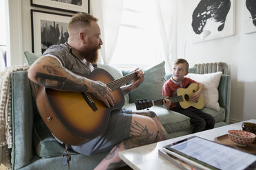 Father with digital tablet teaching son playing guitar in living room - HEROF18748