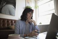 Focused woman working at laptop in living room - HEROF18772