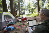 Man using laptop at campsite in woods - HEROF18805