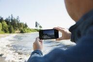 Man using camera phone on sunny beach - HEROF18829