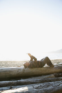 Man laying on driftwood log using cell phone on sunny beach - HEROF18835