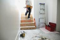 Man with caulk gun descending stairs toward home improvement project - HEROF18865