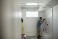 Man using caulk gun at wall for home improvement project - HEROF18868