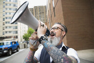 Hipster with beard and tattoos using megaphone in city - HEROF18901