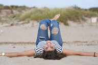 Spain, Menorca, portrait of smiling young woman lying on back on the beach - IGGF00762
