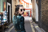 London, young woman walking in Chinatown, turning - IGGF00766