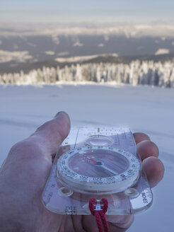 Germany, Upper Bavarian Forest Nature Park, man's hand holding compass in winter - HUSF00014