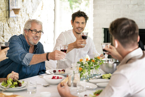 Happy family having meal together clinking wine glasses - PESF01280