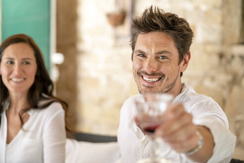 Portrait of smiling man raising his red wine glass - PESF01292