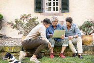 Three happy men of different age using laptop in garden - PESF01295