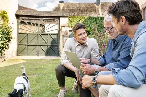 Three smiling men of different age using tablet in garden - PESF01298