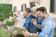 Three men of different age having a video chat via tablet in garden - PESF01301