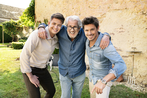 Portrait of three happy men of different age embracing in garden - PESF01304