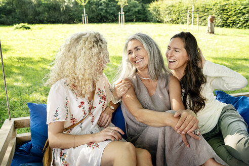 Three happy women of different age sittingon a hanging bed in garden talking - PESF01307