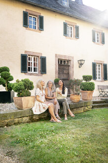 Three smiling women of different age sitting at country house talking - PESF01310