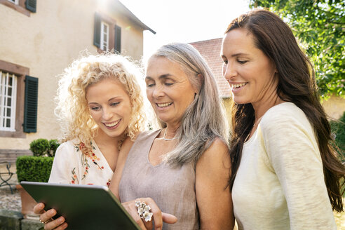 Three smiling women of different age using tablet in garden - PESF01313
