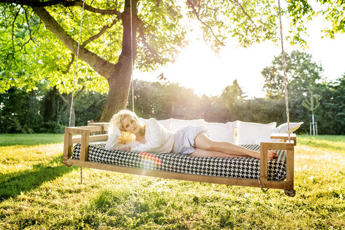 Portrait of young lying on a hanging bed in garden - PESF01343