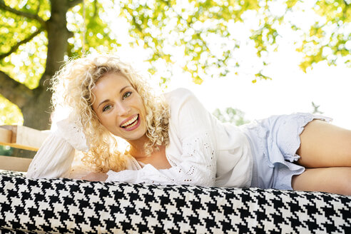 Happy young woman lying on a bed in garden - PESF01346