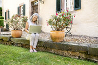 Woman with long grey hair sitting on terrace at country house using laptop - PESF01349