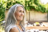 Portrait of smiling woman with long grey hair in garden - PESF01364