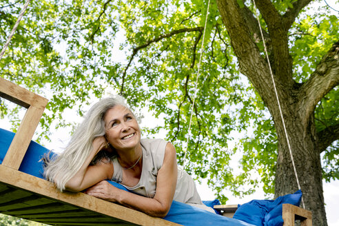 Smiling woman with long grey hair lying on a bed in garden - PESF01367