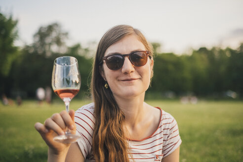 Portrait of smiling woman wearing sunglasses toasting with glass of wine at city park - JSCF00134
