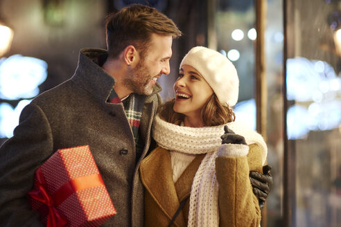 Happy couple on shopping tour at Christmas time looking at each other - ABIF01155