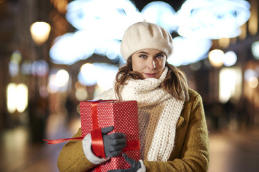 Portrait of smiling woman with Christmas present in the evening - ABIF01158