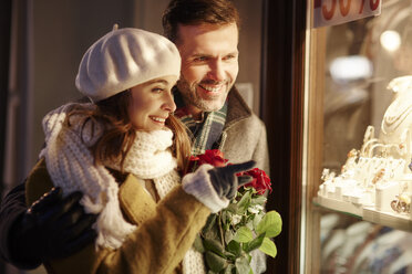 Smiling couple looking in shop window of jewellery store at Christmas time - ABIF01161