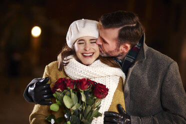 Man kissing his laughing girlfriend in winter - ABIF01164