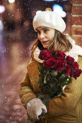 Portrait of young woman with bunch of red roses in winter - ABIF01167
