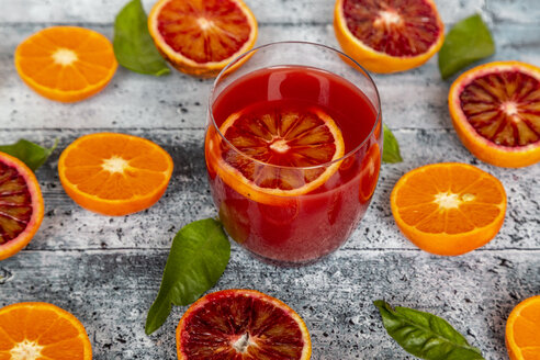 Glass of blood orange juice and halves of blood oranges and tangerines - SARF04098