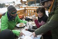 Mature friend skiers enjoying breakfast, preparing with map on ski resort balcony - HEROF19063
