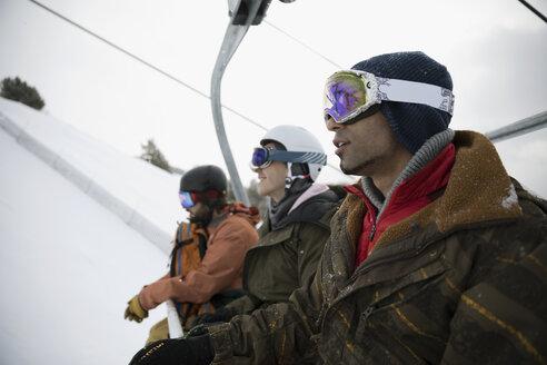 Male snowboarder friends riding ski lift - HEROF19078