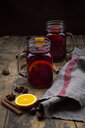 Glasses of mulled wine with cranberries, cinnamon sticks, orange and star anise on dark wood - LVF07758