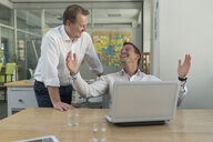 Two businessmen with laptop talking in office - PAF01855