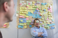 Businessman with sticky note sticking at his forehead in office - PAF01882