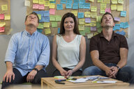 Portrait of colleagues sitting in front of wall with sticky notes in office - PAF01888