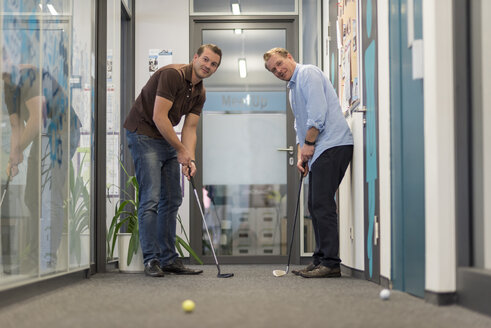 Two businessmen playing golf in office - PAF01903