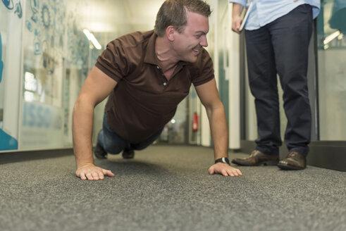 Businessman doing push-ups on office floor - PAF01909