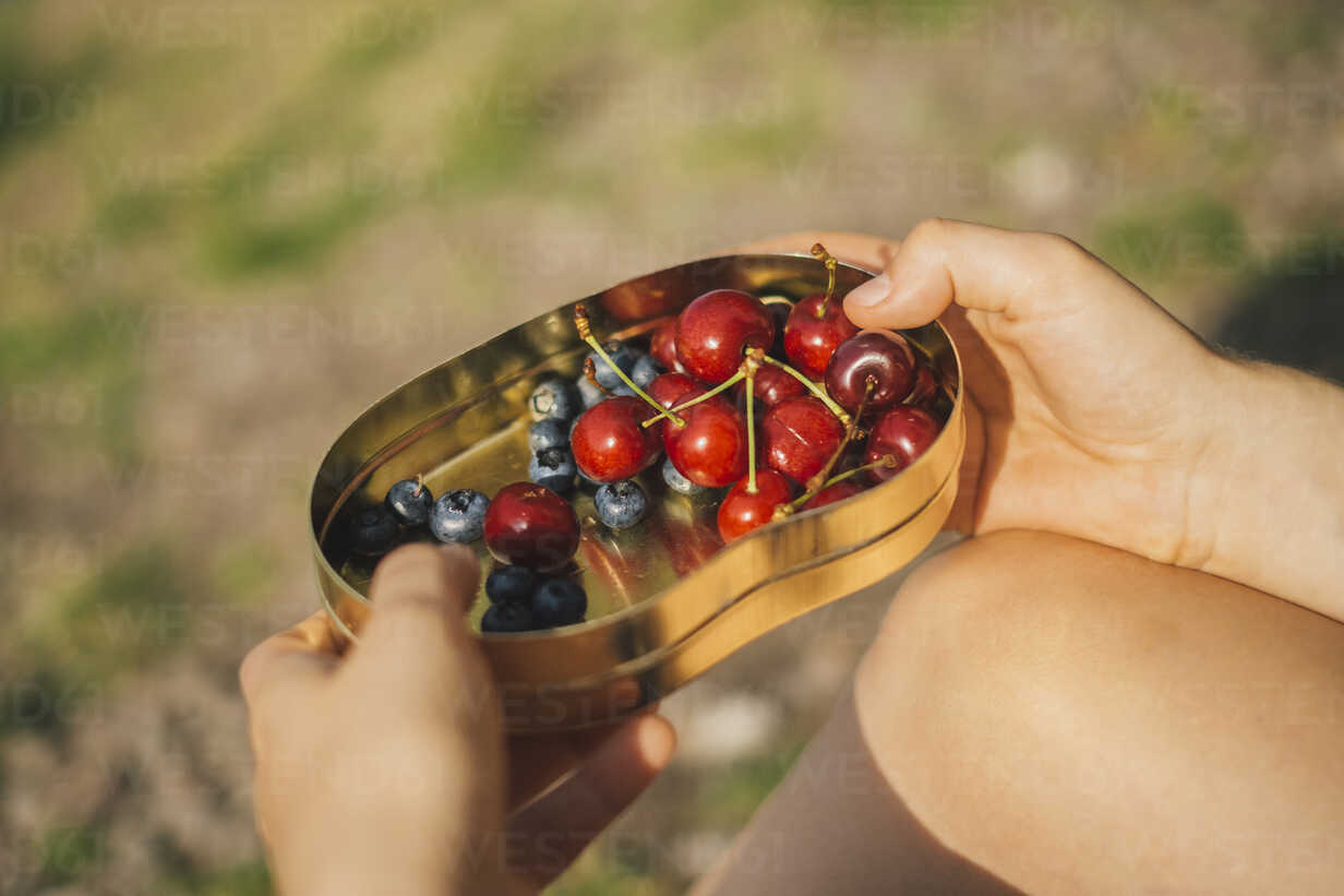Woman's hand holding can of cherries and blueberries, close-up - JSCF00137 - Jonathan Schöps/Westend61