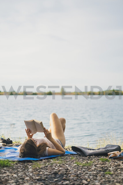 Young woman lying on blanket at lakeshore reading a book - JSCF00140
