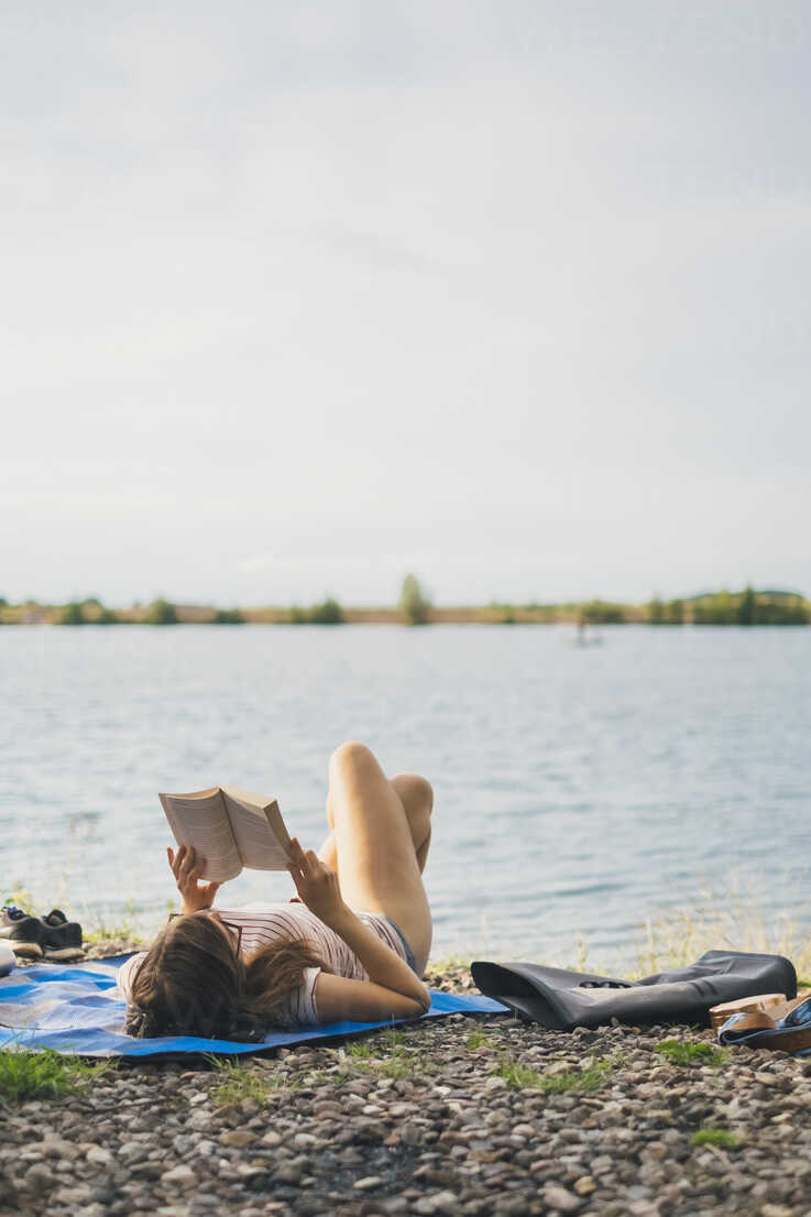 Young woman lying on blanket at lakeshore reading a book - JSCF00140 - Jonathan Schöps/Westend61