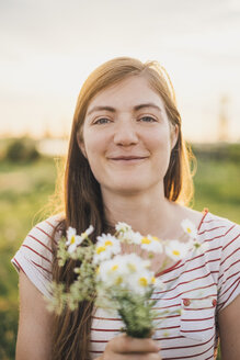 Portrait of smiling young woman holding bunch of picked wildflowers - JSCF00143