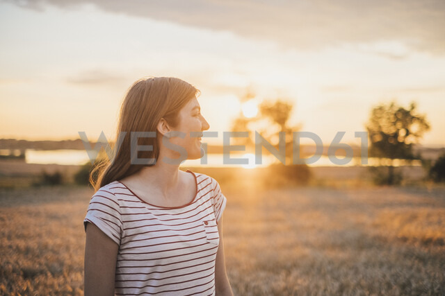 Smiling young woman enjoying sunset in nature - JSCF00149 - Jonathan Schöps/Westend61