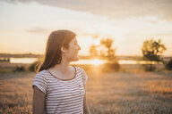 Smiling young woman enjoying sunset in nature - JSCF00149