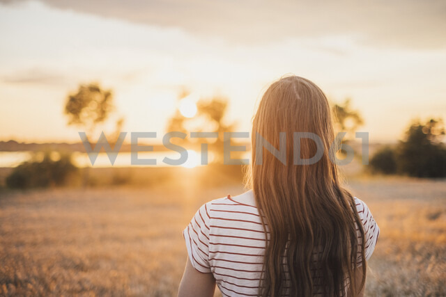 Back view of young woman watching sunset - JSCF00152 - Jonathan Schöps/Westend61