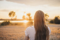 Back view of young woman watching sunset - JSCF00152