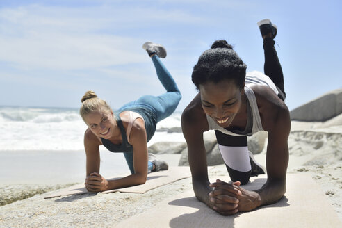 Two women doing a fitness exercise on the beach - ECPF00388